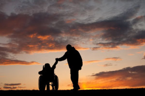 A man holding hands with someone in a wheel chair.